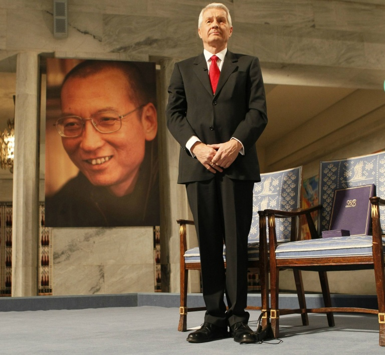 "Chairman of the Norwegian Nobel Committee Thorbjoern Jagland stands near the empty chair where this year's Nobel Peace Prize winner jailed Chinese dissident Liu Xiaobo would have sat, on which his Nobel certificate and medal have been placed, as a portrait of Liu is seen in the background, during the ceremony at Oslo City Hall December 10, 2010. Chinese dissident Liu Xiaobo was awarded the Nobel Peace Prize in an Oslo ceremony derided by Beijing as a farce, and dedicated it from his prison cell to the ""lost souls"" of the 1989 Tiananmen Square crackdown. REUTERS/Heiko Junge/Scanpix Norway/Pool (NORWAY - Tags: POLITICS ANNIVERSARY IMAGES OF THE DAY) NO COMMERCIAL OR BOOK SALES. THIS IMAGE HAS BEEN SUPPLIED BY A THIRD PARTY. IT IS DISTRIBUTED, EXACTLY AS RECEIVED BY REUTERS, AS A SERVICE TO CLIENTS. NORWAY OUT. NO COMMERCIAL OR EDITORIAL SALES IN NORWAY"