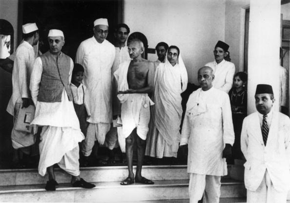 9th June 1939: Indian thinker, statesman and nationalist leader Mahatma Gandhi (Mohandas Karamchand Gandhi, 1869 - 1948), centre, waiting for a car outside Bifla House, Bombay, on his return from Rajkoy. Amongst the group with him are Pandit Nehru (1869 - 1964) (left) and Vallabhai Patel (right). (Photo by Keystone/Getty Images)